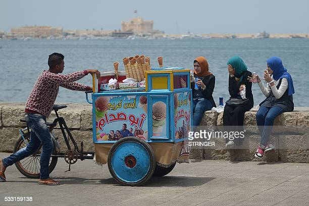 TOPSHOT An Egyptian ice cream vendor pushes his cart on May 21 2016 in the coastal Egyptian city of Alexandria / AFP / STRINGER