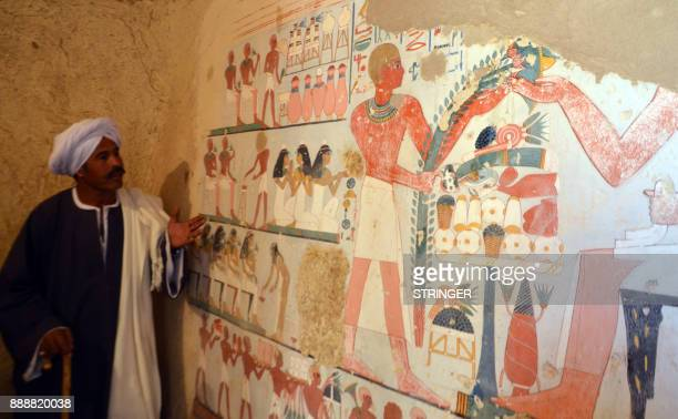 An Egyptian labourer stands next to an ancient Egyptian mural found at the newly discovered Kampp 161 tomb at Draa Abul Naga necropolis on the west...