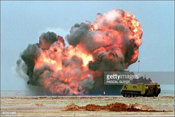 An Egyptian light armoured vehicle explodes 25 February 1991 after driving over an Iraqi mine on the second day of the massive ground assault of the...