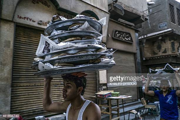 An Egyptian man carries on his head meals for Iftar as he delivers them for Muslims customers to break their daylong fast during the holy month of...