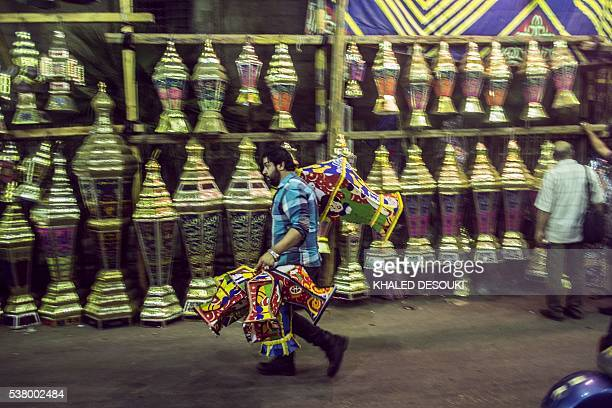 An Egyptian man carries traditional lanterns known in Arabic as 'Fanous' sold during the Muslim holy month of Ramadan in the capital Cairo on June 2...