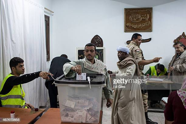 An Egyptian man casts his vote at a polling booth in the district of Mohandessin on January 14 2014 in Cairo Egypt Some clashes between protesters...