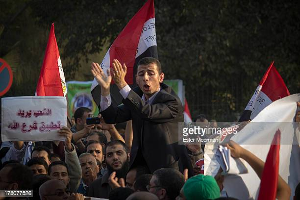 CONTENT] An Egyptian man chants and claps as he leads a crowd at a rally held in support of the Muslim Brotherhood and their president Mohammed Morsi...
