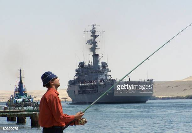 An Egyptian man fishes of a pier while the French navy helicopter carrier Jeanne D'Arc passes through the Suez Canal in the port city of Ismailia 120...