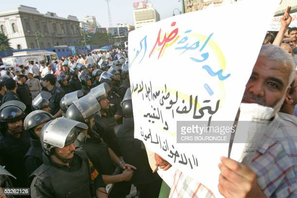 An Egyptian man holds a banner reading 'one hand against corruption' during a rally staged in Cairo 20 July 2005 by the Muslim Brotherhood joined by...