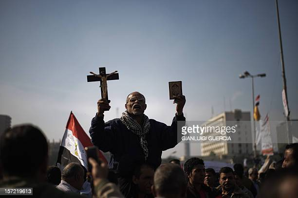 An Egyptian man holds a copy of the Koran and a cross as thousands protesters gather in Cairo's landmark Tahrir square on November 30 to protest...