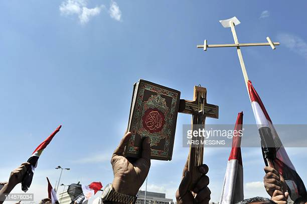 An Egyptian man holds a Koran Islam's holy book as others raise crosses during a protest in central Cairo on March 11 2011 as hundreds of Egyptians...