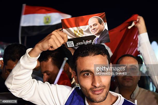 An Egyptian man holds a picture depicting Egyptian President Abdel Fattah alSisi and reading 'Long live Egypt' during a march in Naama Bay a popular...