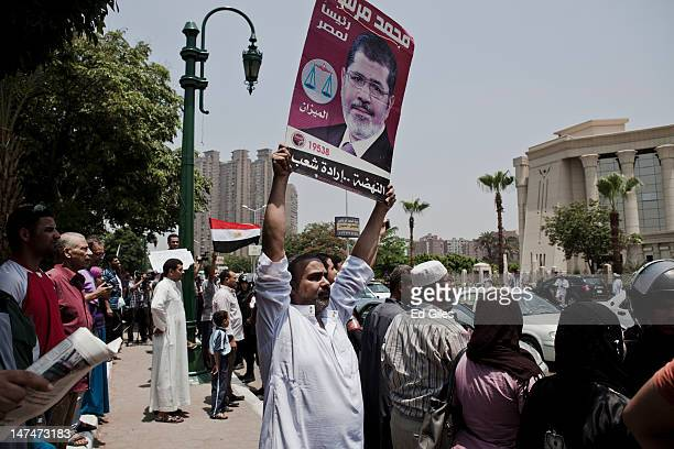 An Egyptian man holds a poster of newly elected President Mohammed Morsi in front of the Supreme Constitutional Court on June 30 2012 in Cairo Egypt...