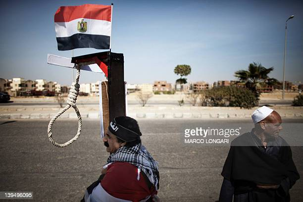 An Egyptian man holds mock gallows with the Egyptian national flag on top during a protest against Hosni Mubarak on February 22 2012 outside the...