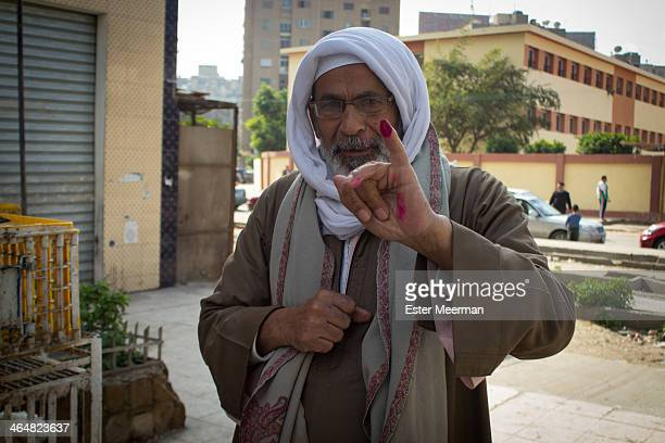 An Egyptian man holds up his purple stained pinky finger outside a polling station in the Cairo suburb of Nasr City, to signify that he has voted in...
