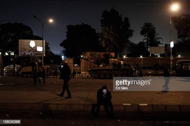 An Egyptian man looks at a mobile phone near a tank of the Egyptian Republican Guard parked by the outer walls of Egypt's Presidential Palace during...