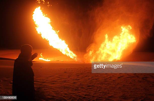 An Egyptian man looks at flames rising from a pipeline that delivers gas to Israel and Jordan after it was hit by an explosion some 40 kilometres...