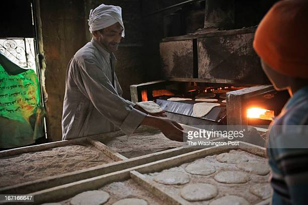 An Egyptian man makes bread with government subsided flour in the City of the Dead a neighborhood of Cairo Egypt Thursday April 11 2013 Egypt's...