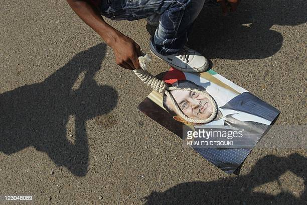 An Egyptian man places a noose on an image of former president Hosni Mubarak as pro and antiMubarak supporters gathered outside the Cairo criminal...
