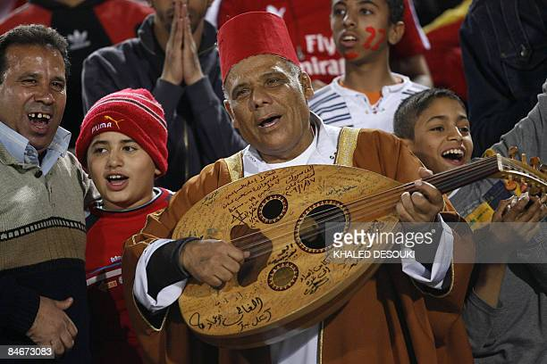An Egyptian man plays the oud as alAhly fans cheer for their team before the start of their African Super Cup final football match against Tunisia's...