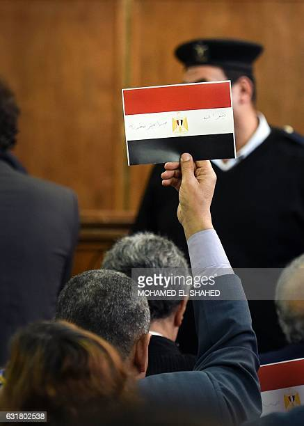An Egyptian man raises a card in a courthouse showing the national flag defaced with the words 'Tiran' and 'Sanafir' after the High Administrative...