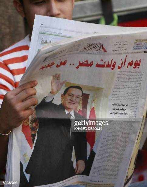 An Egyptian man reads a copy of AlAhram newspaper with a frontpage picture of President Hosni Mubarak reading 'The day Egypt was born again' in Cairo...