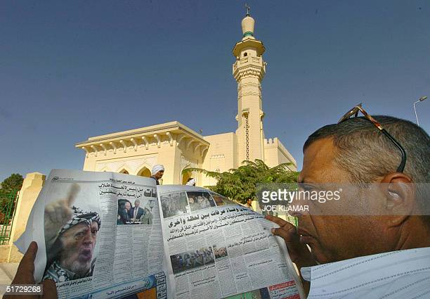 An Egyptian man reads a local newspaper in front of the King Faisal Mosque 11 November 2004 close to the international airport in Cairo where the...