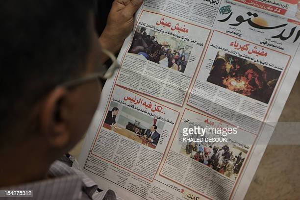 An Egyptian man reads the independent AlDostour newspaper published in Cairo on August 19 2010 with the frontpage featuring an opposition slogan with...