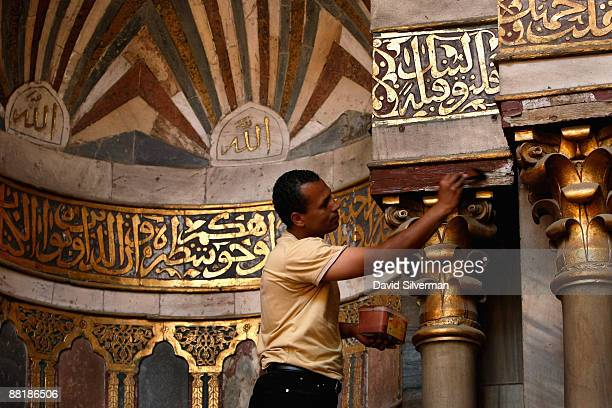 An Egyptian man repaints the woodwork around the mihrab the prayer niche as workers rush to prepare the Sultan Hassan mosque one day ahead of the...