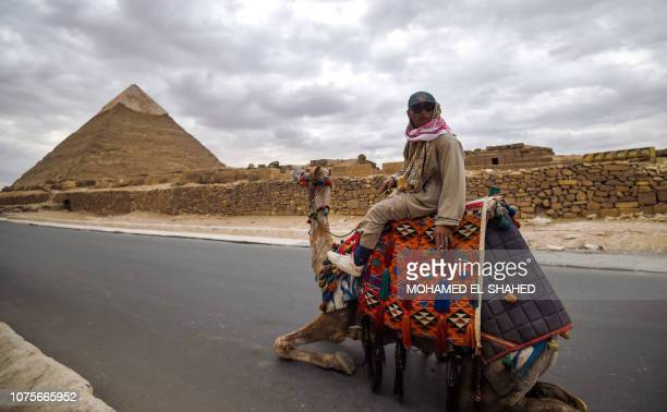 An Egyptian man rides a camel at the Giza pyramids necropolis on the southwestern outskirts of the Egyptian capital Cairo on December 29 with the...