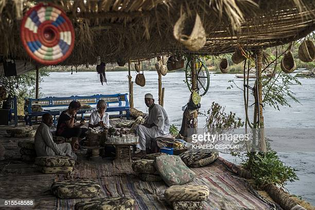An Egyptian man serves coffee to German tourists at traditional cafe on the banks of the Nile River in Aswan some 900 kilometres south of Cairo on...