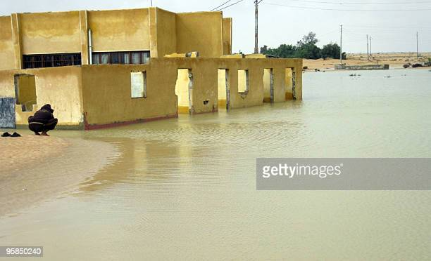 An Egyptian man squats in front of a flooded area in the Egyptian port town of ElArish 45 kilometres from the Gaza border as heavy rains and floods...