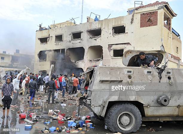An Egyptian man stands in an armoured vehicle as residents gather outside a police station in North Sinai's provincial capital of ElArish after it...