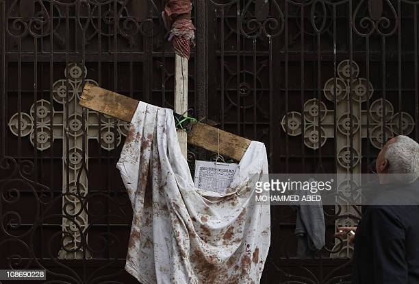 An Egyptian man stands on January 2 2011 next to a bloodstained piece of cloth hung outside the AlQiddisine church in the Mediterranean port city of...