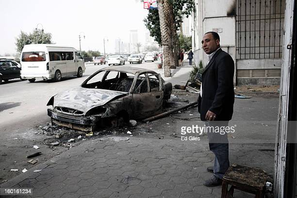 An Egyptian man stands on the street by the wreckage of a car damaged in violent clashes the previous night near Tahrir Square on January 27 2013 in...
