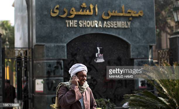 An Egyptian man talks on his mobile phone outside the Shura Council the upper house of parliament where the Constituent Assembly drafted the...