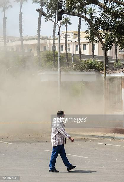 An Egyptian man walks as a bomb struck a police post near Cairo University in the centre of Egypt's capital on April 2 which was followed by two...