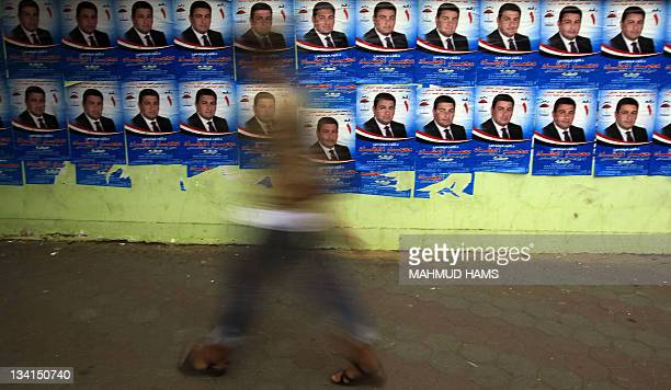 An Egyptian man walks past campaign posters for candidate Mohammed alAqqad in Cairo on November 27 2011 on the eve of the first parliament elections...