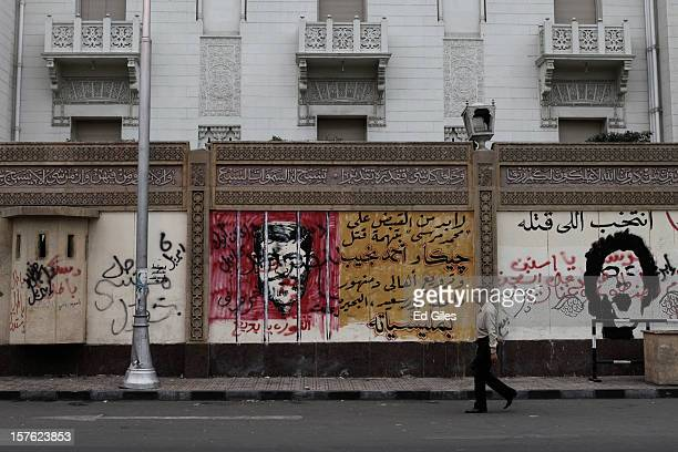 An Egyptian man walks past graffiti painted by protesters during a demonstration against Egyptian President Mohammed Morsi the previous night on the...