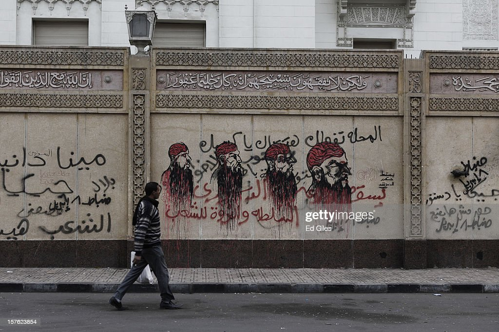 An Egyptian man walks past graffiti painted by protesters, during a demonstration against Egyptian President Mohammed Morsi the previous night, on the walls of the Presidential Palace on December 5 in Cairo, Egypt. Thousands of protesters converged on the Presidential Palace in the Cairo suburb of Heliopolis on December 4 to demonstrate against the country's draft constitution that was rushed through parliament in an overnight session on November 29. Protesters and police briefly clashes outside the Presidential Palace on Tuesday evening before riot police retreated inside the palace grounds. The country's new draft constitution, passed by a constitutional assembly dominated by Islamists, will go to a referendum on December 15. (Photo by Ed Giles/Getty Images).