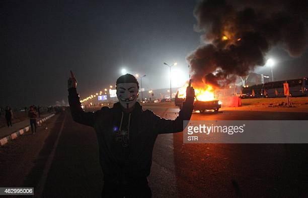 An Egyptian man wearing a mask of the anonymous movement gestures near a burning car outside a sports stadium in a Cairo's northeast district on...