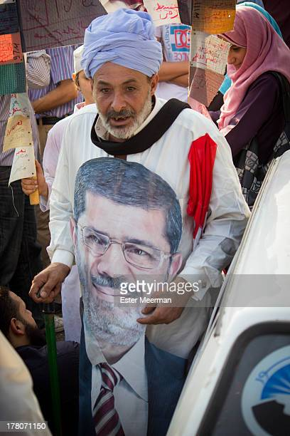 An Egyptian man wears a traditional Egyptian garment known as a galabiyya, with a print of president's Mohammed Morsi's face on it.