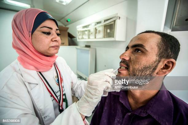 An Egyptian medical staffer takes oral samples from a labourer undergoing examination for Hepatitis C at the construction site of Egypt's new...