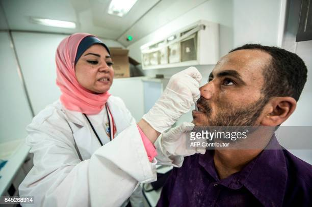 An Egyptian medical staffer takes oral samples from a labourer undergoing examination for Hepatitis C at a construction site in Egypt's new...