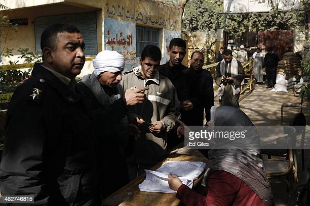 An Egyptian men stand in line to cast their votes at a polling booth on January 15 2014 in the rural district of Fayoum Egypt Egyptians went to the...