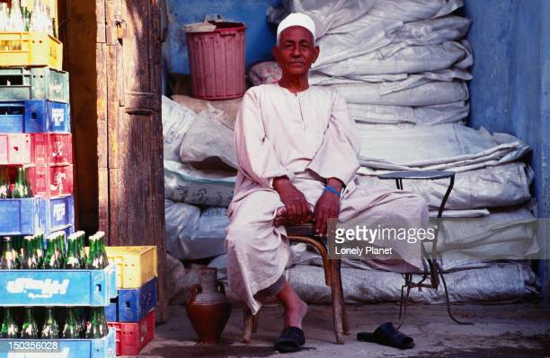 An Egyptian merchant sits patiently on his chair waiting for business.