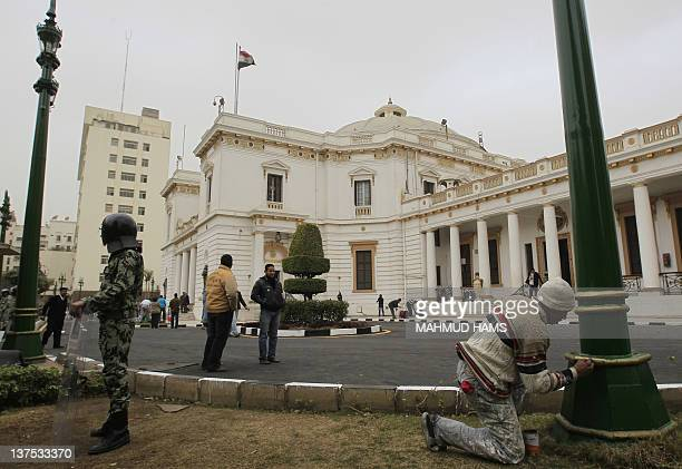 An Egyptian military policeman stands guard as workers clean and paint the parliament building premises in Cairo on January 22 2012 Egypt's newly...