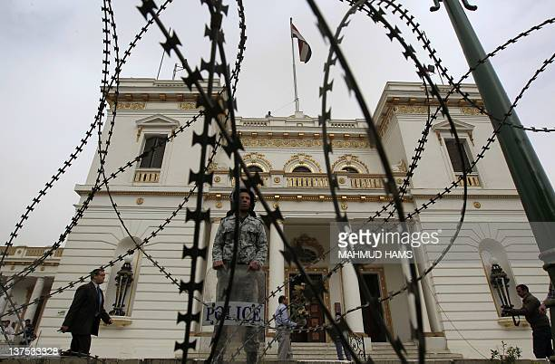 An Egyptian military policeman stands guard behind barbed wire fence as workers paint and clean the parliament building in Cairo on January 22 2012...