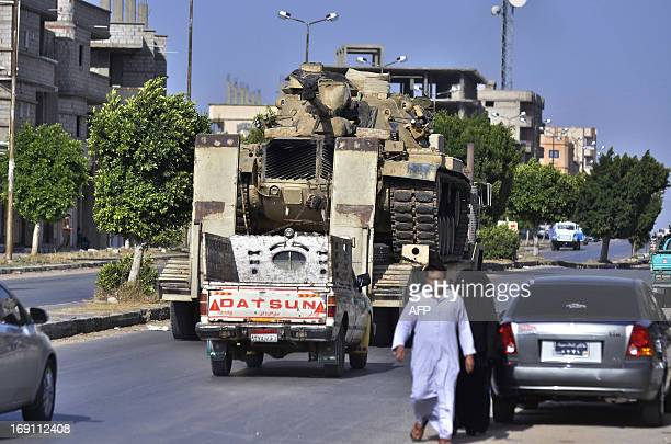 An Egyptian military truck carries a tank through the Sheikh Zowied town near Rafah on May 20 to be deployed in alArish city in the northern Sinai...