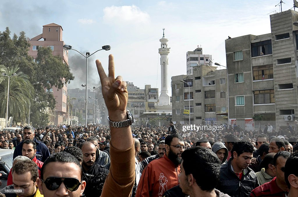 An Egyptian mourner flashes the sign for victory as mourners march in the canal city of Port Said on January 28, 2013 during the funeral of six people killed in clashes the day before, which were triggered after a court sentenced 21 people to death over a football riot that killed more than 70 people last year. A state of emergency came into force in three Egyptian provinces Port Said, Suez and Ismailiya which have been hit by deadly rioting, as President Mohamed Morsi scrambled to contain deepening divisions with calls for a national dialogue.