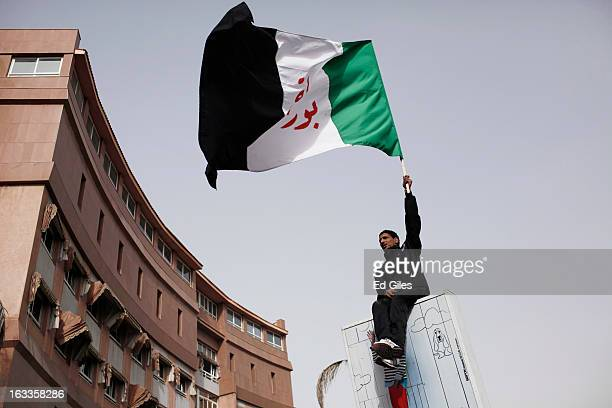 An Egyptian mourner waves the Port Said flag prior to a funeral procession for a demonstrator Ahmed Abdul Khalim killed in violent clashes with...