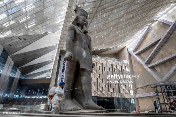 An Egyptian municipality worker disinfects the area around the 3,200-year-old pink-granite colossal statue of King Ramses II, as a protective measure...