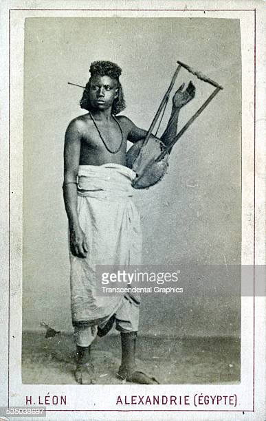 An Egyptian musician poses in the studio of H Leon with his favorite instrument in Alexandria Egypt around 1860
