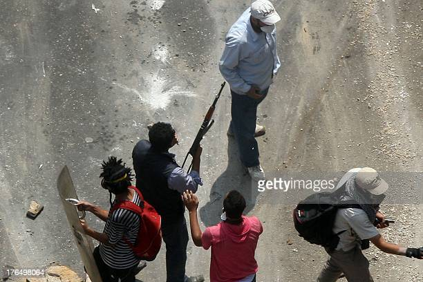 An Egyptian Muslim brotherhood supporter of Egypt's ousted president Mohamed Morsi carries an AK47 as another holds up a rito police shield during...